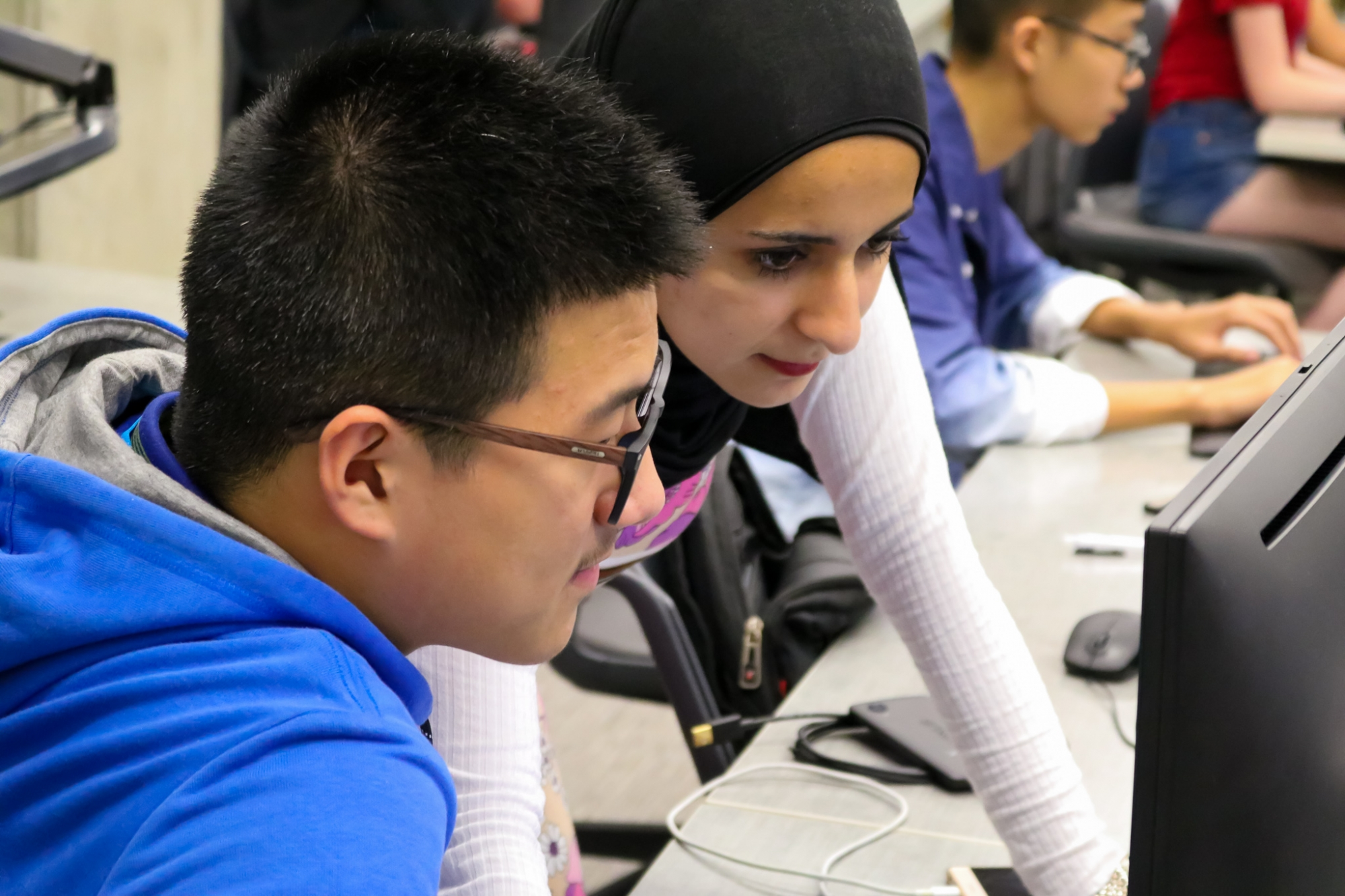 Student and Course Assistant looking over a computer