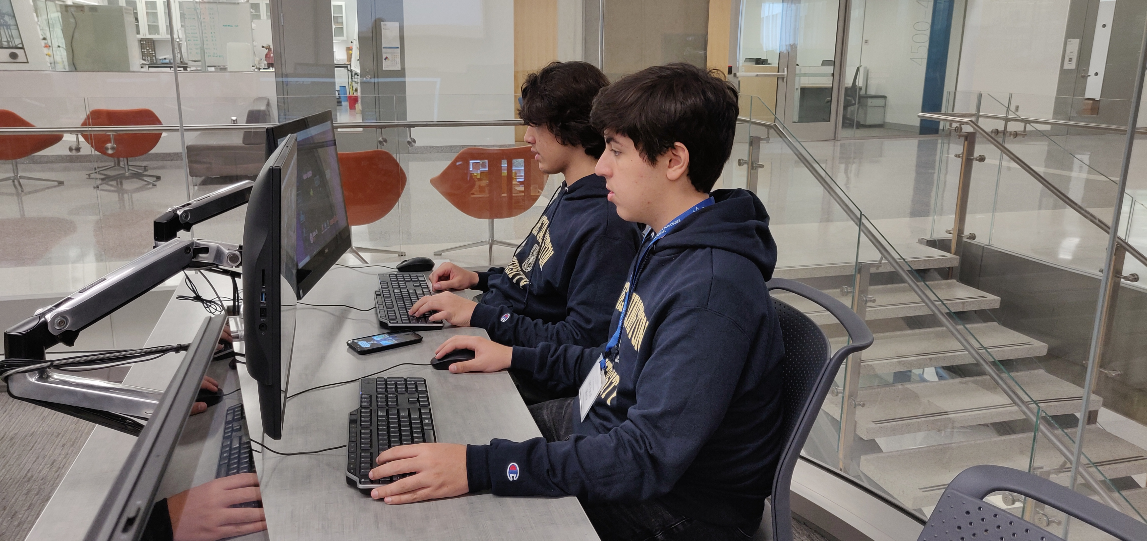 Students at a computer typing computer code
