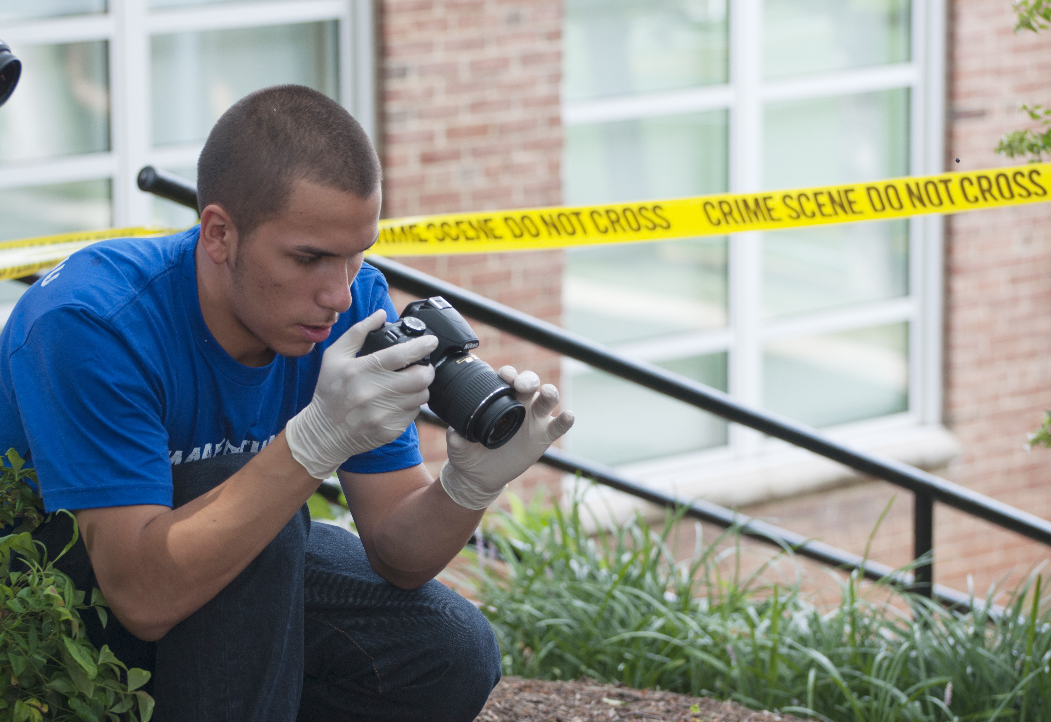 Student taking a photo to inspect a mock crime scene