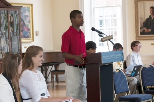 A student speaking at a podium in front of other students and adults.