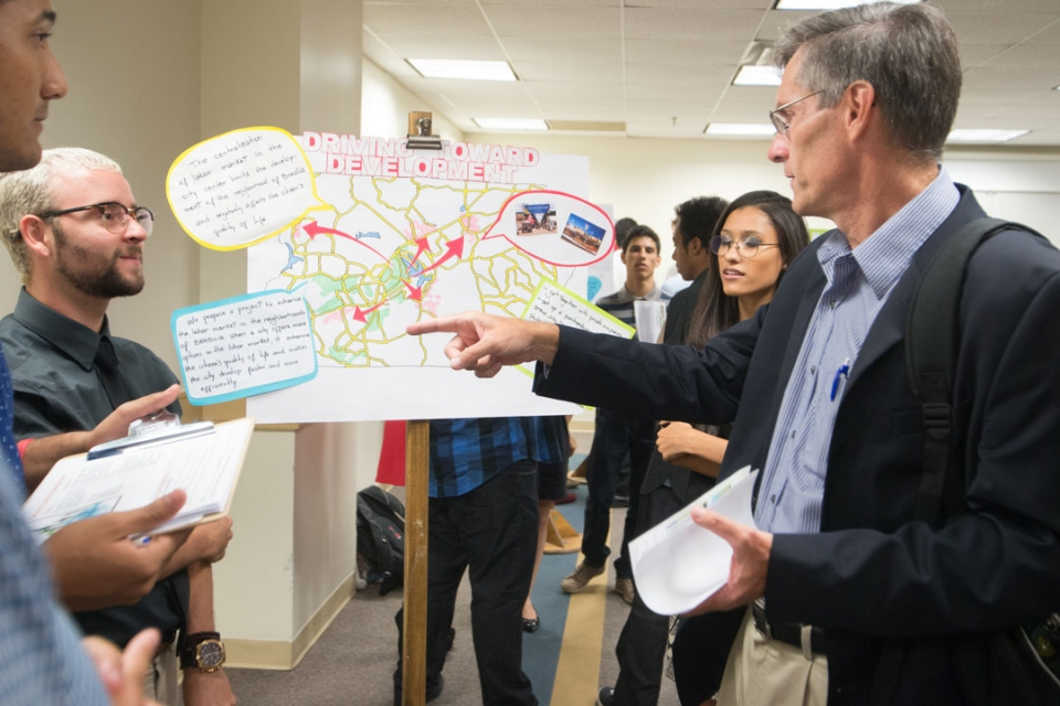 Students in the Brasilia Without Borders program sharing poster project with professor