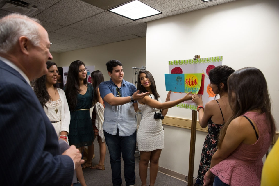 Students in the Brasilia Without Borders program sharing poster project with President Knapp