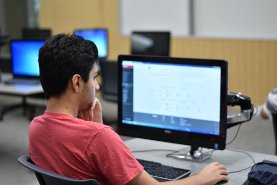 Photo of student sitting at a computer