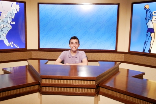 A student in the Newseum sitting at a mock news desk.