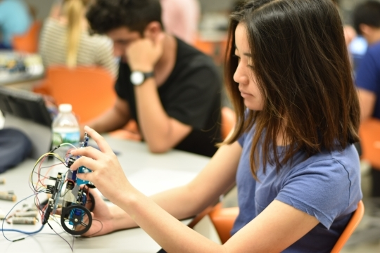 Robotics student building robot in class lab